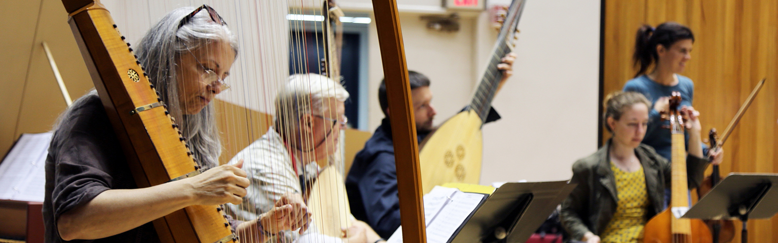 Faculty and participants playing a harp and other early music instruments at a workshop at MEMF 2015